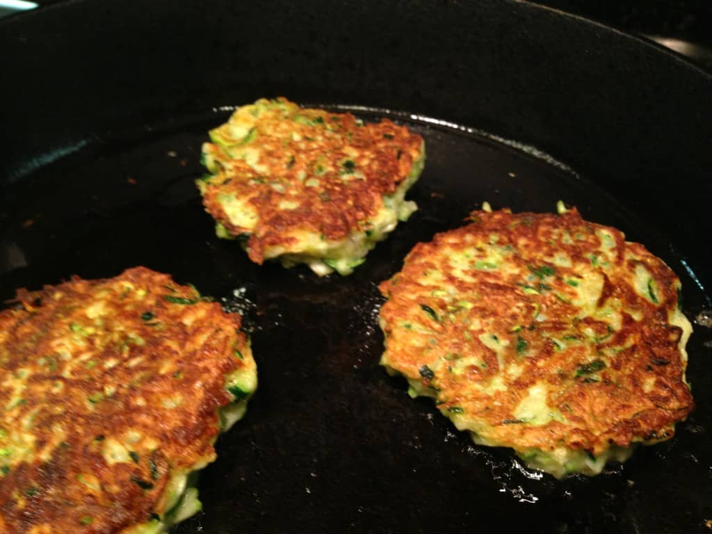 Zucchini fritters in the frying pan.