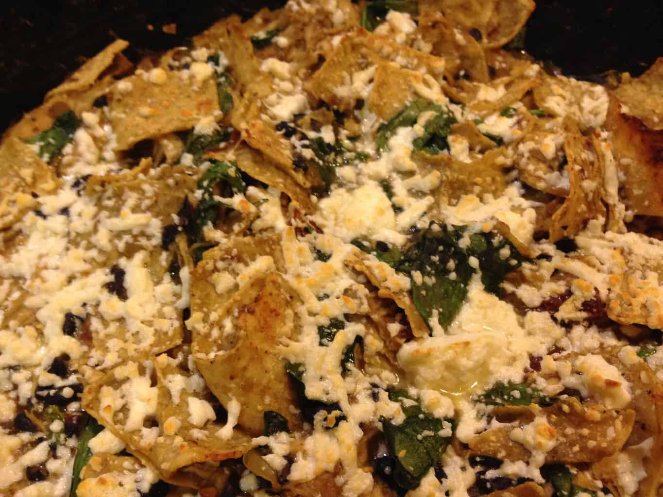 Chilaquiles with cheese, spinach, and chicken.