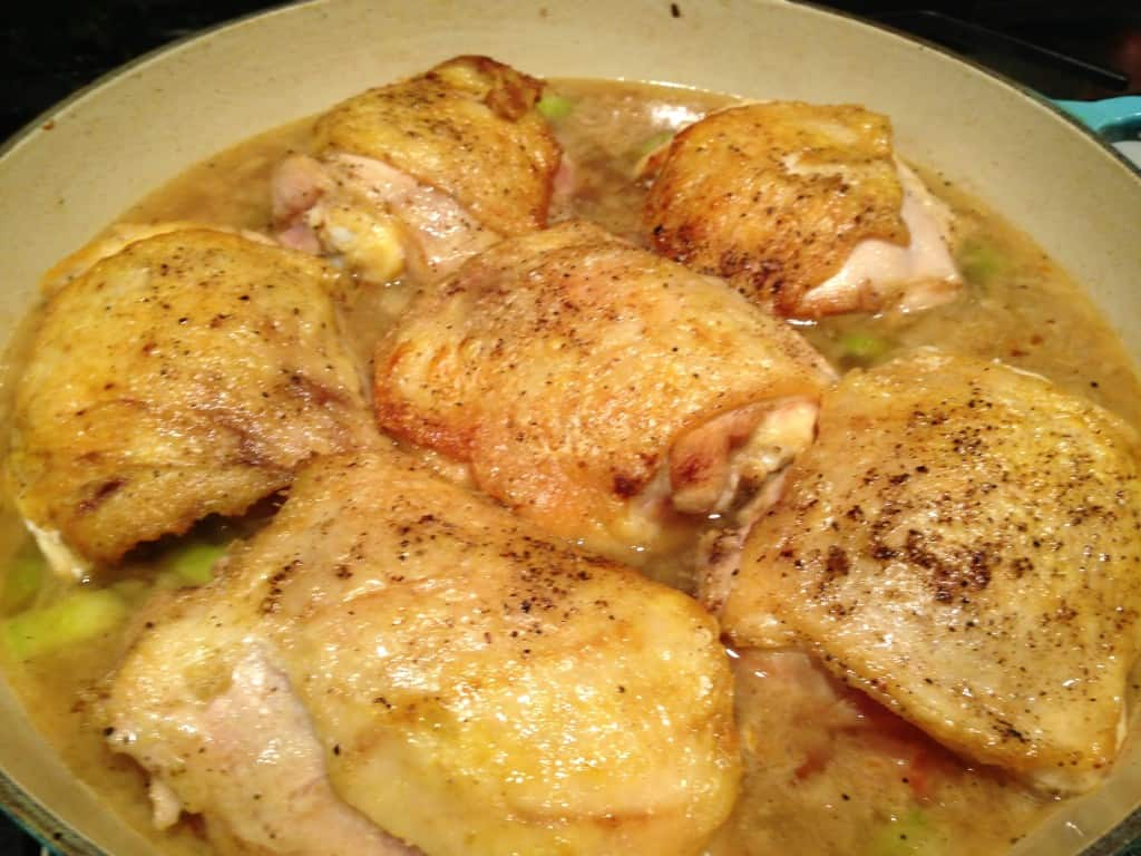 Browned chicken in braising sauce.